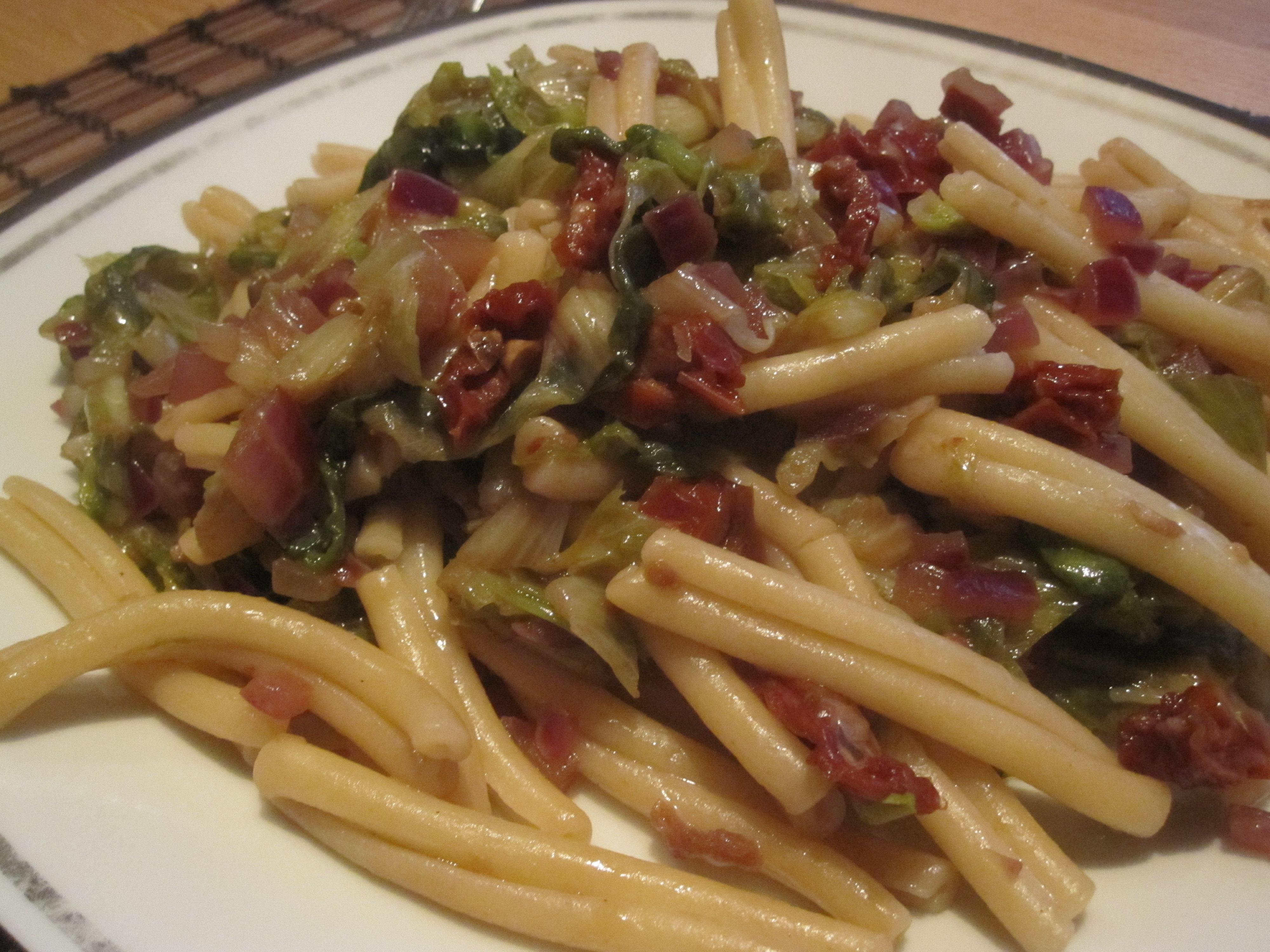 Strozzapreti met andijvie, zongedroogde tomaten en parmezaanse kaas